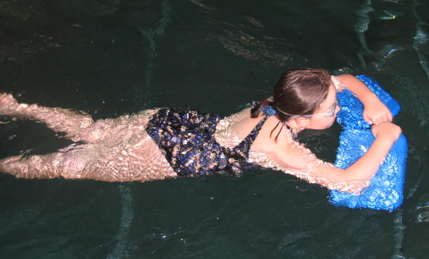 teaching a child to swim with floats